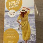 Op de foto de cover van het boek Zon, Zee en blote voeten. Een vrouw met rood half lang haar en een gele zomerjurk staat met haar rug naar de camera en op haar blote voeten in de zee. Ze staart over het water, terwijl ze met haar linkerhand getekende slippers vasthoudt en met haar rechterhand haar witte hoedje met zwarte strik..